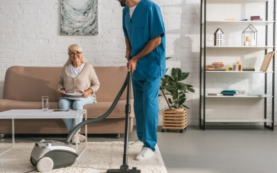 senior woman relaxing on a couch while a caregiver vacuums the carpet