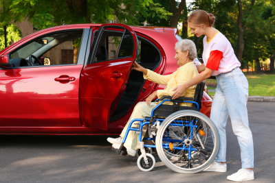 young woman helping a senior on a wheelchair get in a car