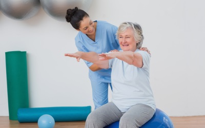 caregiver helping a senior woman exercise