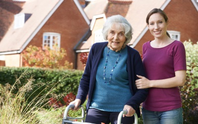 senior woman on a walking frame with her young caregiver