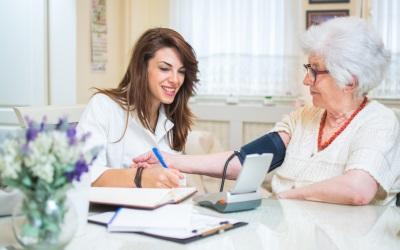 nurse checking her senior patient's blood pressure