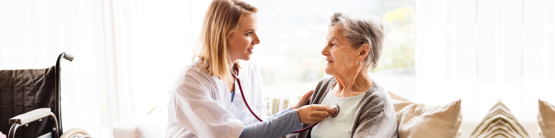 caregiver using her stethoscope on her senior patient