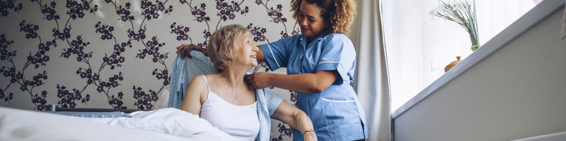 caregiver helping a senior woman put on clothes