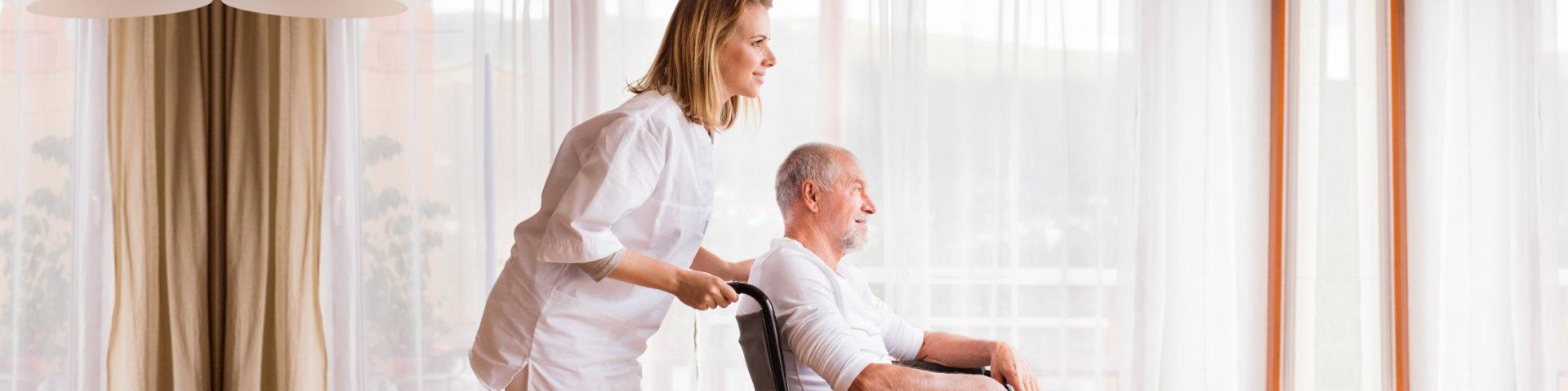 caregiver assisting a senior man on a wheelchair